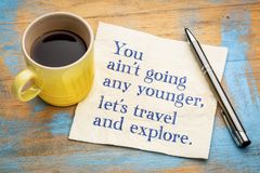 You are not going any younger, let us travel. You ain`t going any younger, let`s travel and explore - handwriting on a napkin with a cup of espresso coffee Stock Image