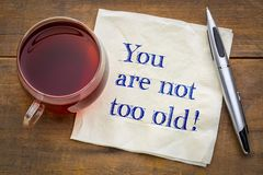 You are not too old!. Positive affirmation, handwriting on a napkin  with a cup of tea Stock Photography