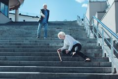 Scared man concerned about his wife falling on stairs royalty free stock photo