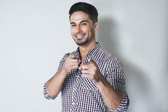 You are the one!. Close up portrait of young handsome smiling man looking and pointing with finger at camera against grey background. Positive expression Stock Image