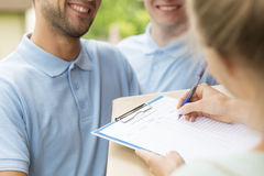 You order we deliver. Close up of a two couriers with a parcel and women signing a delivery form Royalty Free Stock Photography
