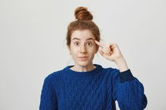 Are you out of your mind. Attractive young european woman with red hair and freckles with bun hairstyle rolling index. Finger near temple, showing shock after royalty free stock photos