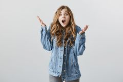 Are you out of your mind. Studio shot of shocked impatient european girlfriend with blond hair in stylish denim jacket. Shaking raised palms and dropping jaw royalty free stock photography