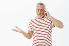 Are you out of your mind. Upset mature dad with white hair and beard in striped t-shirt raising palm in clueless gesture. Rolling index finger on temple being stock photos