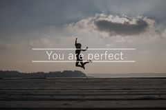 You are perfect sign. Over a happy woman jumping in air against sky with sun behind cloud stock photo