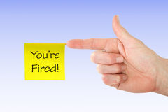 You're Fired!. White hand pointing finger with a yellow you're fired note attached royalty free stock photos