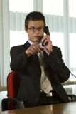 You're Fired. A young male executive on the phone and pointing into the camera Stock Image