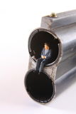 You're Fired. Miniature business man sitting in barrel of shotgun Royalty Free Stock Image