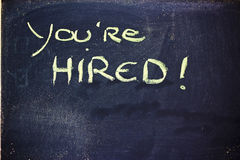 You're hired message on chalkboard. Chalk writings on blackboard, you're hired Royalty Free Stock Photo