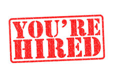 YOU`RE HIRED Rubber Stamp. Over a white background Stock Photos