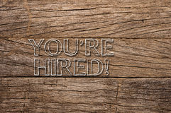 You're hired written on wooden background Royalty Free Stock Image
