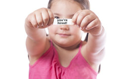 You`re hired. Young girl holding a fortune cookie paper with the message You`re hired Royalty Free Stock Image