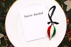 You're Invited. Blank white paper with words YOU'RE INVITED and vintage Christmas ornament on top of round white dinner plate Stock Photo