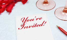 You're Invited!. A note paper with the words You're Invited! written in red script with interlocking Y and I Stock Photography