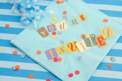 You're invited. Cut out letters spelling you're invited on baby blue napkins with curled ribbons and confetti, great for invitation cards Royalty Free Stock Images