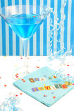 You're invited invitation. You're invited spelled out with cut out letters on blue napkin with blue martini with confetti and curled ribbons great for party Stock Photo