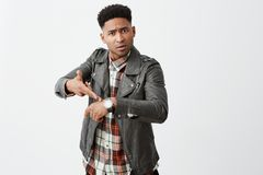 You`re late. Portrait of angry beautiful black-skinned mature guy with afro hairstyle in leather jacket pointing on hand Stock Image