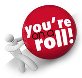 You're On A Roll Man Pushing Ball Up Hill Momentum Streak. You're On a Roll words on a ball pushed by a man up a hill to symbolize succeeding on a winning streak royalty free illustration
