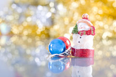 You're too big to hold you. Snowman-like candle holding a little tree in hand, red and blue Christmas balls in front of golden and silver garland Stock Photo