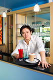 You're welcome here. The cafe's owner offering us welcoming drinks Stock Photography