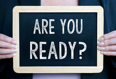 Are you ready - Businesswoman holding chalkboard with text. In her hands stock photo