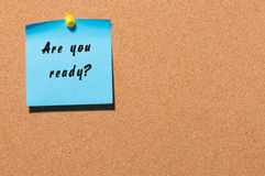Are You Ready, written on an blue sticky note on a cork bulletin board. With empty space for text Royalty Free Stock Photo