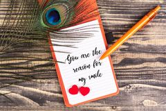 You are the reason for my smile. Text in notebook with peacock feather , pen and heart shape on wood royalty free stock images