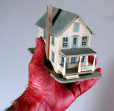 Are you in the red. Red hand holding a house royalty free stock image