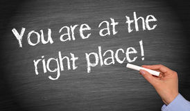 You are at the right place chalkboard. You are at the right place - female hand with chalk writing text on chalkboard or blackboard stock photography
