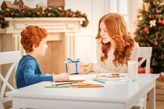 Loving mother giving son christmas present. This is for you. Selective focus on a mature lady smiling while sitting next to her amazed son and giving him a tiny Royalty Free Stock Photos