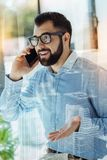 Handsome astonished man talking on the cellphone gesticulating. Are you serious. Handsome astonished nice-looking man keeping right hand near his head talking Stock Photos