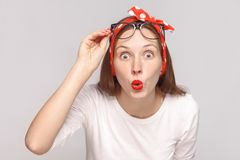 Are you serious? portrait of wondered surprised young woman in w. Hite t-shirt with freckles, glasses, red lips and head band looking at camera with big eyes royalty free stock photography