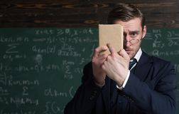 You should better learn it. Teacher formal wear and glasses looks smart, chalkboard background. Man unshaven holds book royalty free stock photos