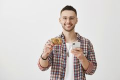 You should get yourself this card. Attractive young coworker holding credit card and smartphone, smiling broadly at. Camera, standing over gray background royalty free stock photo