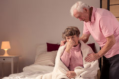 You should go to bed. Ill senior women sitting on a bed and her husband supporting her Stock Photos