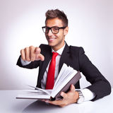 You should read too!. Young business man at his desk reading a book and choosing you to read it too Royalty Free Stock Images