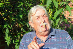 You smell bad. An elderly man with a peg on his nose and pointing towards the camera. indicating where the smell is coming from stock photos