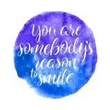You are sombodys reason to smile. Hand-drawn calligraphy on a blue watercolor background Royalty Free Stock Photography
