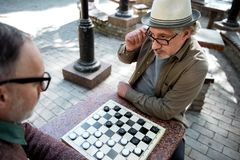 Pensive senior male pensioners playing chequers. Are you sure with this move. Top view of serious mature men looking at his opponent in checker game with Stock Images
