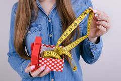 You are too fat! Go to gym! Cropped closeup photo of astonished fatty lady holding opening unpacking unwrapping package with. Yellow meter  grey background stock photos