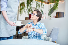 You are too late!. Irritated middle-aged cafe visitor pointing at wristwatch with displeasure while unrecognizable waitress serving coffee Stock Photos