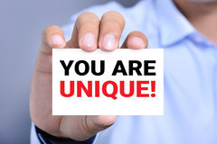 YOU ARE UNIQUE !, message on the card hold by a man Stock Image