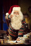 You've been a naughty boy!. Angry Santa Claus poiting finger at camera and leaning to his messy desk Royalty Free Stock Photos
