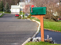 You've Got Mail. A green mailbox with a red arm; the arm lifted to signal mail pick-up. Tranquil suburban setting in sunset light Stock Photos