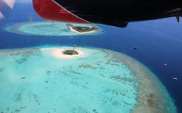 You`ve reached your destination: Maldives. Seaplane over twin islands Maafushivaru and Lonubo in Ari Atoll, Maldives, Indian ocean Royalty Free Stock Images
