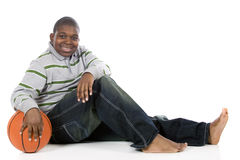 You 'Wanna Play?. A happy preteen boy relaxing with his basketball, looking like he's ready to play.  Isolated on white Stock Photography