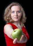 You want?. Beautiful woman in a red dress with a green apple in a hand on a black background.  Focus on an apple, and the woman on a background also is dim Stock Photo