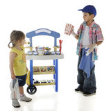 You Wanted Popcorn?. A young candy and snack entrpreneur questioning his preschool customer about her choice of popcorn. The stand's signs are intentionally left stock photo