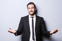 You are welcome!. Cheerful young man in formalwear looking at camera and gesturing while standing against grey background Stock Images