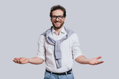 You are welcome!. Handsome young man in smart casual clothes gesturing and smiling while standing against grey background Stock Photography